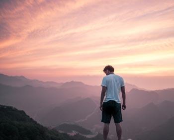 """Bild: Junger Mann in weißem T-Shirt und Shorts, der auf einem Berg steht und die gesamte Landschaft überblickt. Der Himmel ist in rosa und goldfarbenes Licht getaucht und zeigt die Morgendämmerung. Bild für den Blogbeitrag """"Die Angst vor dir selbst - du bist viel mehr als du glaubtest"""" auf daniela-lasinger.at. Photo by Pete Bellis on Unsplash.com."""