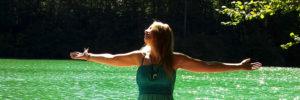 Bild: Daniela Lasinger in grünem Kleid mit ausgebreiteten Armen vor einem See. copyright Daniela Lasinger.
