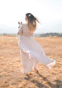 Bild: Junge Frau mit weißer Kleidung trägt Hund in den Armen und spaziert am Sandstrand. Beitragsbild für Artikel zur Stärkung der Intiution auf https://daniela-lasinger.at Bild by pete-bellis on Unsplash.com.